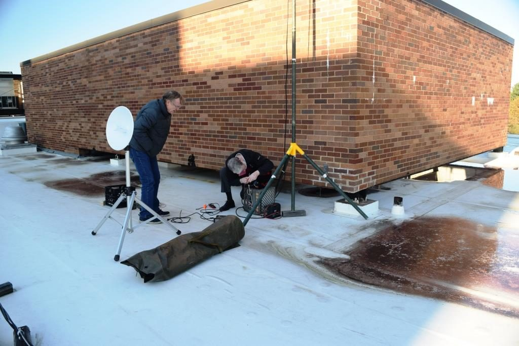 Keit6h, KC3TCB, looks on as Al, KN3U, hooks up the radio on a chilly rooftop.